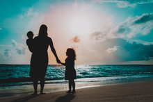 Mother With Two Kids Walking On Beach At Sunset