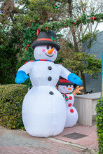 Inflatable Snowman With A Smaller One Next To Him With Christmas Decoration Placed Outdoors.