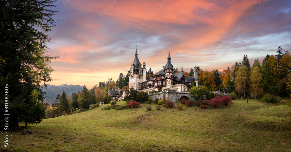 Fototapeta Panorama of Peles Castle, Romania. Beautiful famous royal castle and ornamental garden in Sinaia landmark of Carpathian Mountains in Europe at sunset. Former Home Of The Romanian Royal Family.