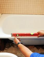 Albañil Comprobando Con Un Nivel La Instalación De Una Nueva Bañera