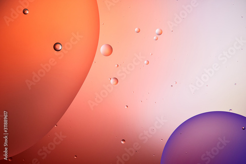 abstract background from mixed water and oil bubbles in red and purple color