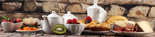 Fototapeta Breakfast served with coffee, orange juice, croissants, cereals and fruits