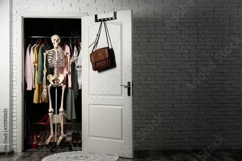 Fotografía  Artificial human skeleton model in wardrobe room, space for text