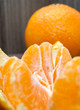 ripe orange or mandarin citrus fruit peeled slices next to the peel in the background a whole orange. vertical