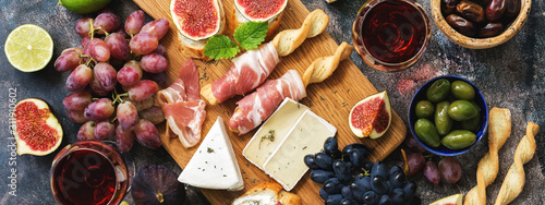 Italian antipasti wine snacks set. Prosciutto,red wine, cheese, olives, grapes, figs and cheese. Top view, banner.
