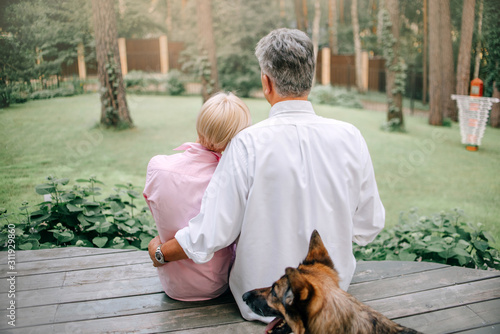 Photo middle aged couple sitting in the backyard together, rear view