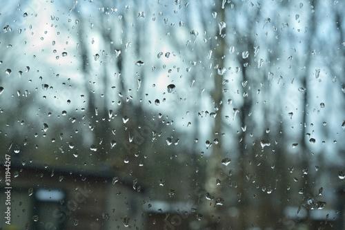 Krople deszczu na szybie, w tle bokeh, nieostre drzewa i domy.