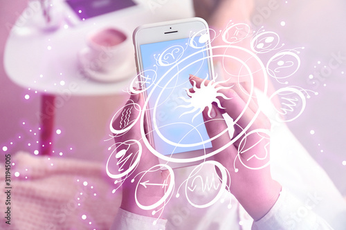 Foto Young woman with mobile phone reading astrological forecast at home, closeup