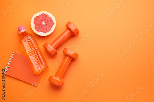 Dumbbells with notebook, grapefruit and bottle of water on color background Obraz na płótnie