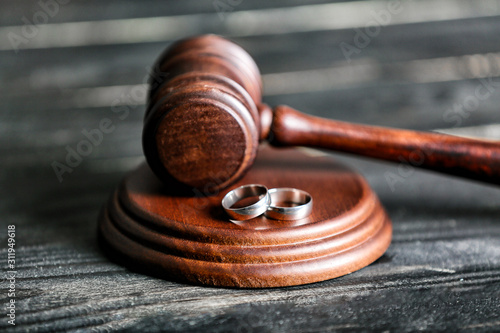 Photo Judge's gavel and rings on wooden background. Concept of divorce
