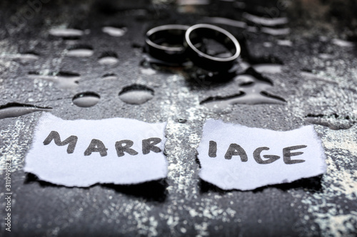 Torn paper with word MARRIAGE and rings on grunge background Wallpaper Mural