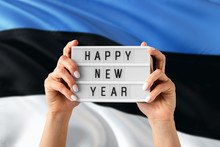 Estonia New Year Concept. Woman Holding Happy New Year Sign With Hands On National Flag Background. Celebration Theme.