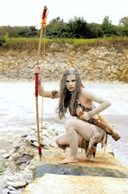 A Young Woman Is  Dressed As A Neanderthal Warrior.  She Is Covered With Mud, Filth And Dirt And Is Seen In  A Stone Quarry Area Surrounding.