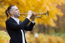 Handsome Male Musician In Black Jacket And White Shirt Plays Golden Shiny Trumpet In Fall Park Against Background Of Autumn Trees With Yellow Leaves