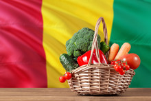Guinea Organic Food Concept. National Flag Background With Basket Full Of Vegetables On Wooden Table. Copy Space For Text.