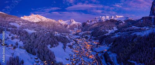 Fototapeta Aerial night view of the Val Gardena ski resort mountain village in Dolomites, Italy, Beautiful cozy village in winter time during Christmas. obraz na płótnie