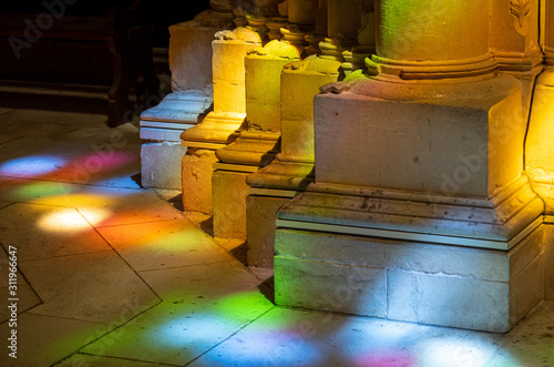 Photo Colored lights from stained glass windows on columns inside the Batalha Monaster