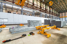 Overhead Crane Beam Hoist Concrete Slab On A Plant For The Production Of Hollow Floor Slabs And New Panels Piled On A Pile For The Construction Of Buildings.