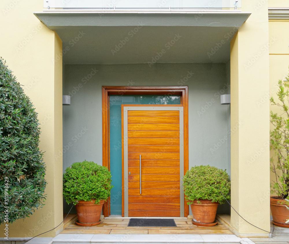 Fototapeta contemporary house cozy entrance wooden door and flower pots