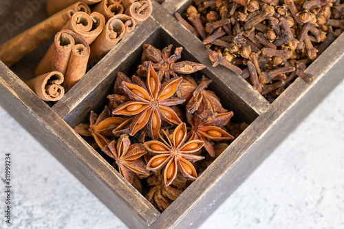 Different spices cinnamon, cloves and star anise on wooden box Wallpaper Mural