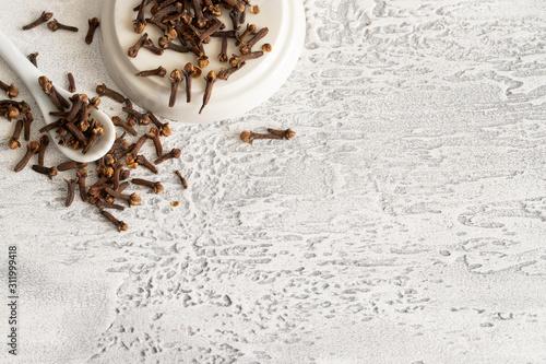 Fototapeta Natural clove spice on ehite concrete background with copy space. obraz