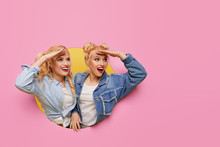 Image Of Two Young Happy Shoked Girlfriends Women. Twins Peeping Through A Pink Hole In The Wall. Big Discount Season. Copy Space For Text