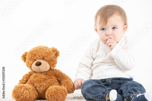 Studio photo Baby with his hand in the mouth with a teddy bear #312007208