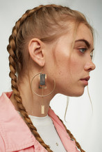 Close-up Shot Of A Blonde Girl With A Golden Earring Made As Unlocked Ring With Right Angled Pendants And A Chain. The Girl With Two Braids Is Wearing A White Top Under A Pink Jeans Jacket.