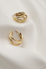 Subject Shot Of A Pair Of Golden Stud Earrings Isolated On The White Textile Surface. Each Earring Is Made In The Form Of A Triple Unlocked Hoop.