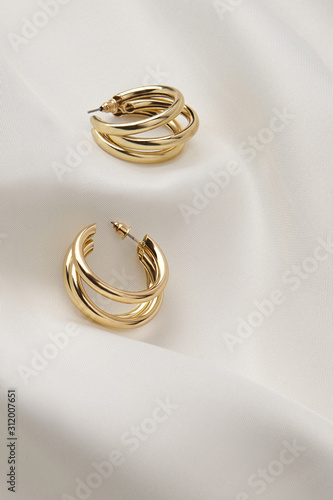 Fototapeta Subject shot of a pair of golden stud earrings isolated on the white textile surface