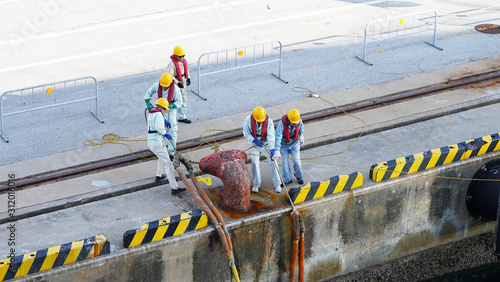 a group of Japanese port workers in uniform and orange helmets fasten ship mooring ropes to the bollard in the port Wallpaper Mural