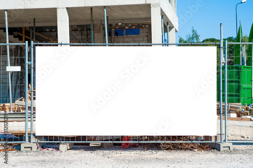 Obraz Blank white banner for advertisement mounted on the fence of construction site on a sunny day. - fototapety do salonu