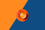 Orange and classic blue background with cup of tasty coffee. Flat lay, top view, copy space. Geometric composition.