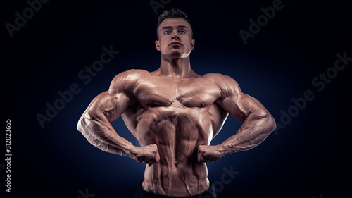 Valokuvatapetti Handsome muscular bodybuilder posing on Front Lat Spread display lat width from