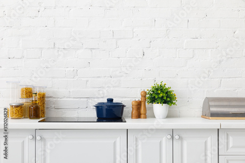Fototapeta modern white kitchen interior with pot on electric induction cooktop near plant