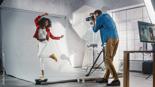 Leinwand Poster Behind the Scenes on Photo Shoot: Beautiful Black Model Poses for a Photographer, he Takes Photos with Professional Camera