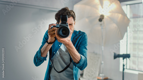 Obraz na plátně In the Photo Studio with Professional Equipment: Portrait of the Famous Photographer Holding State of the Art Camera Taking Pictures with Softboxes Flashing in Background