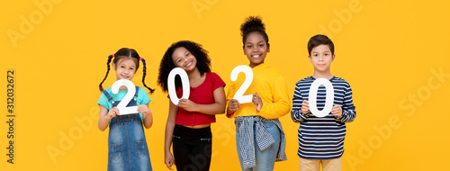 Foto  Mixed race children smiling and holding 2020 numbers on banner backround