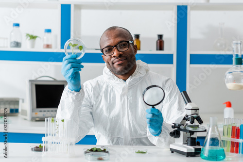 Photo smiling african american biologist holding magnifying glass and leaves