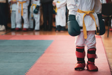 Martial Art. The Kid At The Competitions In Kimano With A Yellow Belt And Big Blue Boxing Gloves To Prepare For The Fight. For Atmospheric Added Film Noise Effect.