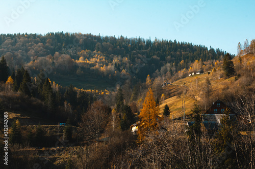Village in the mountains. A beautiful sunny landscape with mountains. Blue sky, grass and forest. Background or wallpaper.