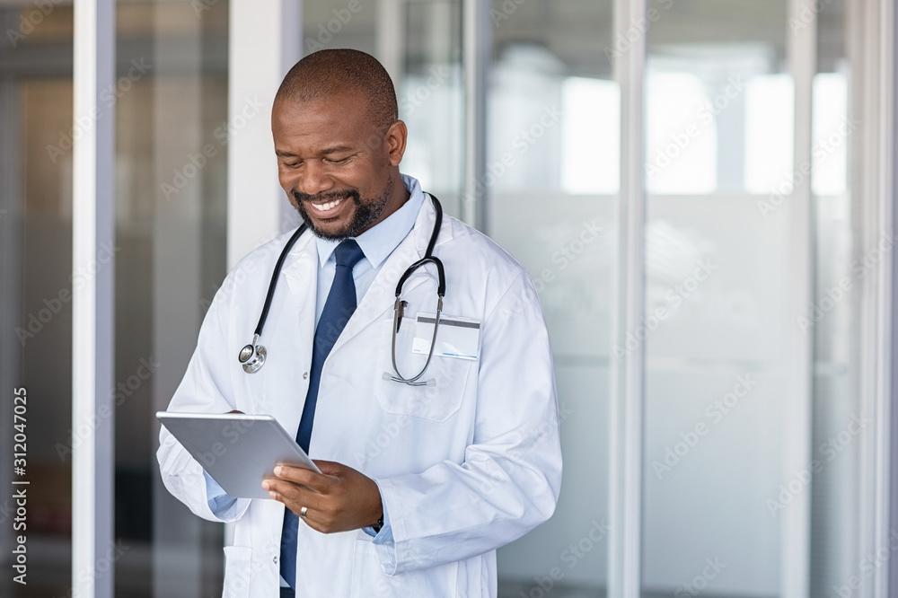 Fototapeta African doctor using digital tablet at hospital