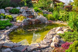 Landscape design of home garden close-up. Beautiful landscaping with small pond and waterfall.