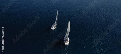 Aerial drone ultra wide photo of beautiful sailboat cruising in Aegean deep blue sea