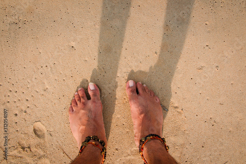 Photo Stand on the white sand beach with beautiful anklets