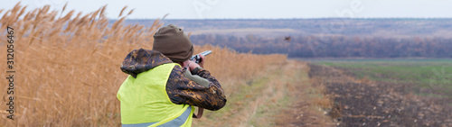 A man with a gun in his hands and an green vest on a pheasant hunt in a wooded area in cloudy weather Canvas Print