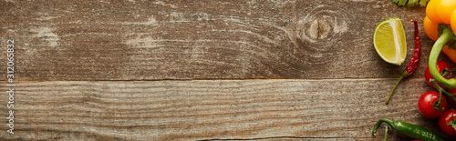 Fotografía  Top view of ripe vegetables and lime slice on wooden background with copy space,