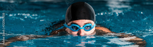 panoramic shot of athletic man in goggles training in swimming pool Wallpaper Mural