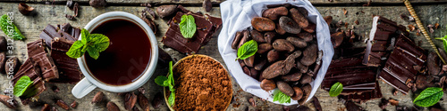 Fototapeta Different conditions of cocoa. Various cocoa - beans, beans, ground, crushed cocoa powder, chocolate paste, chocolate pieces and hot chocolate in a cup. On a wooden rustic background with copy space f obraz