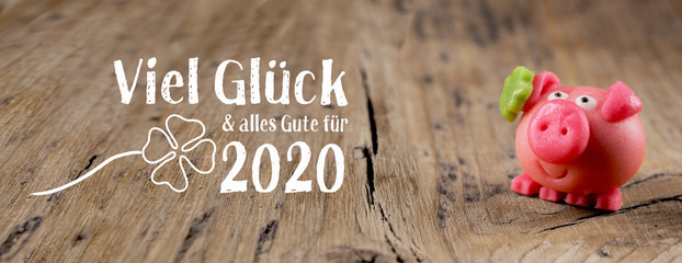 New year card 2020, german language  -  Good luck and best wishes for 2020 -  Marzipan pig on rustic wooden background  -  Good luck symbol
